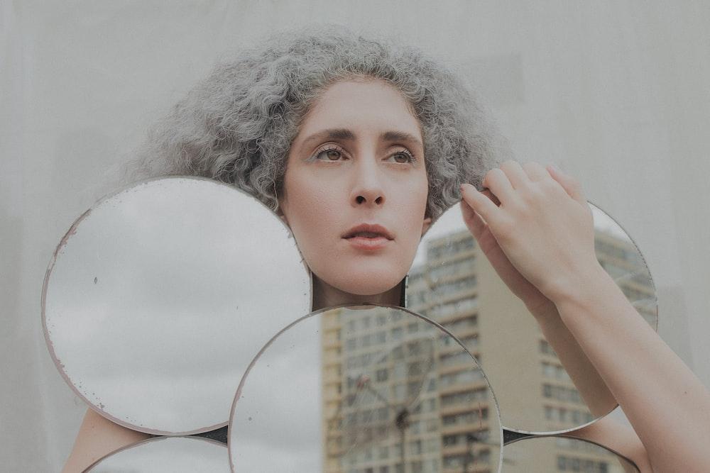 woman holding white round mirror