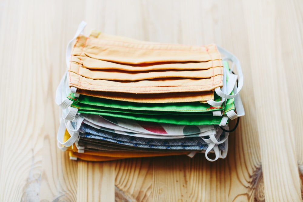stack of white yellow green and blue textiles