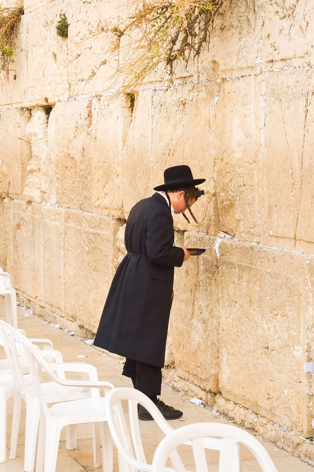 woman in black coat and black skirt standing beside brown concrete wall during daytime