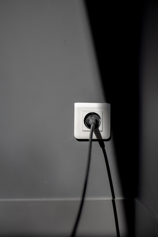 black electric plug on white socket