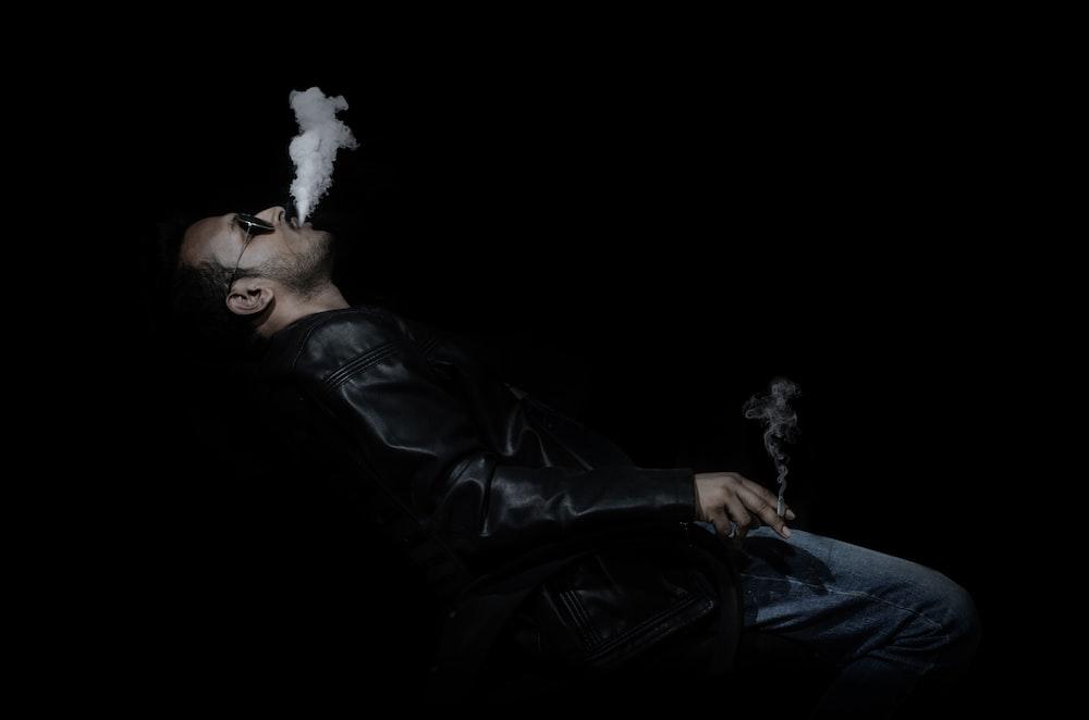 man in black leather jacket smoking