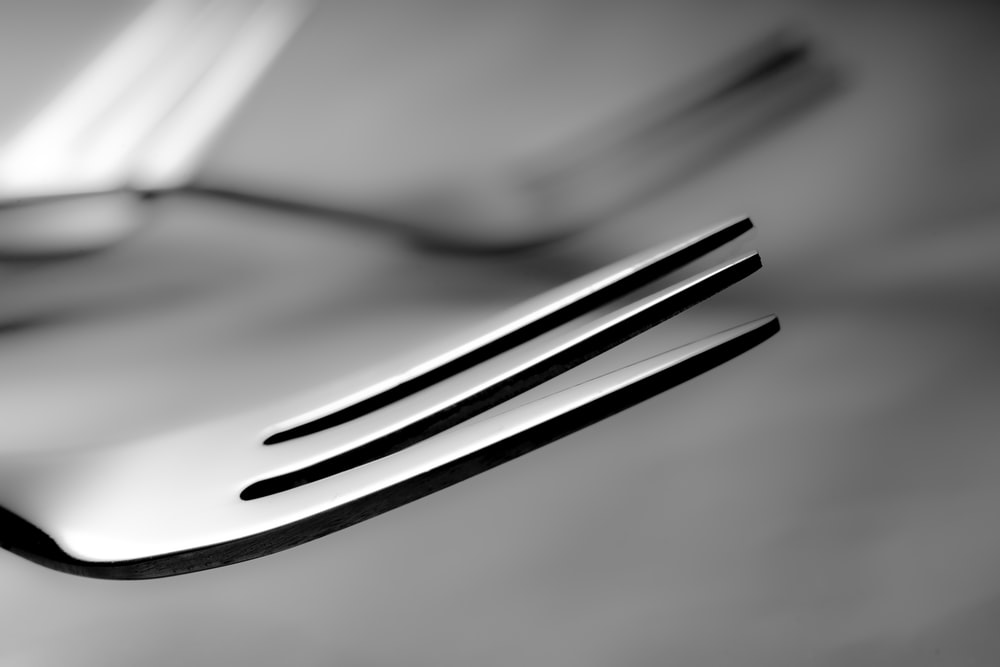 stainless steel fork on white paper
