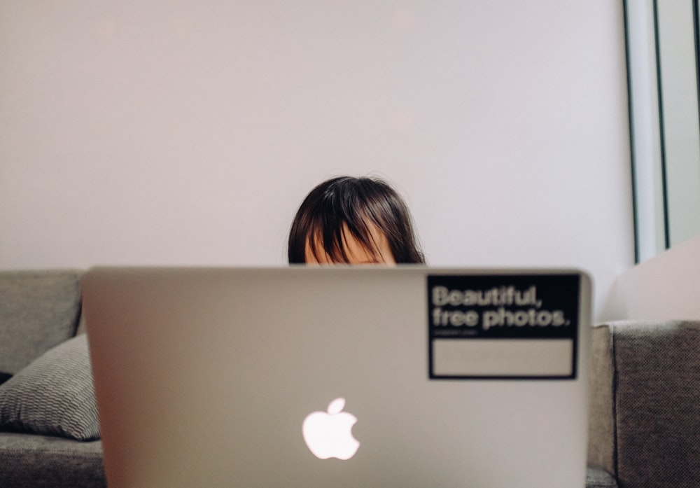woman in front of silver macbook