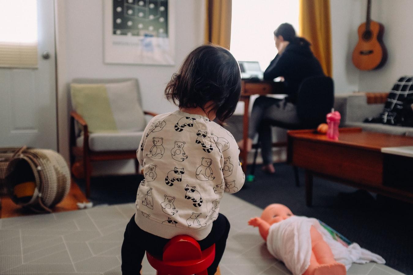 Kind spielt auf dem Boden während das Elternteil im Hintergrund arbeitet