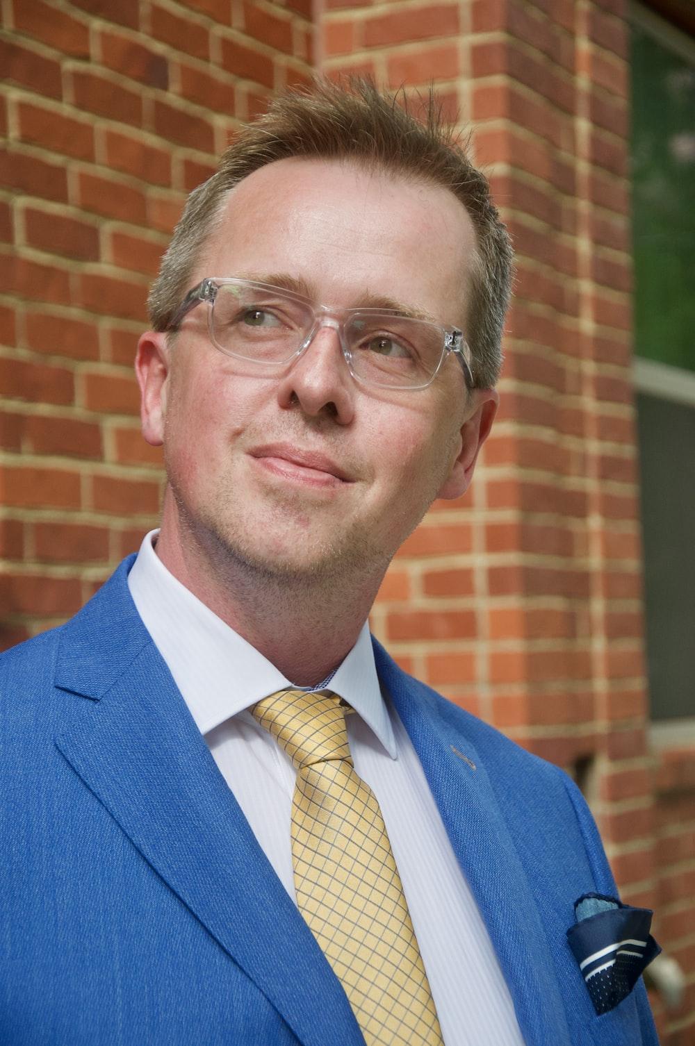 man in blue suit jacket wearing eyeglasses