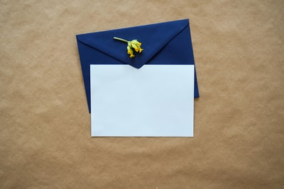 white and blue paper on brown textile letter zoom background