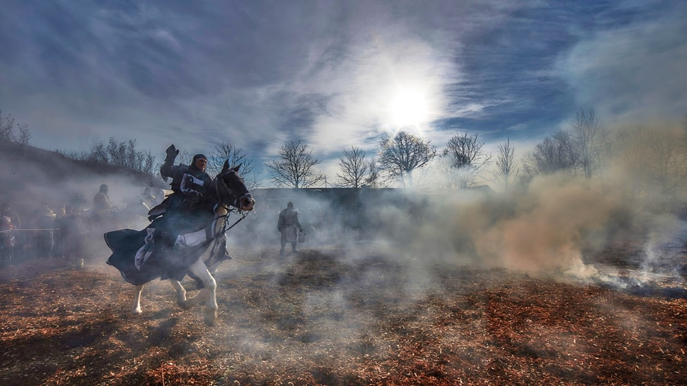 man riding horse on brown field under white clouds during daytime