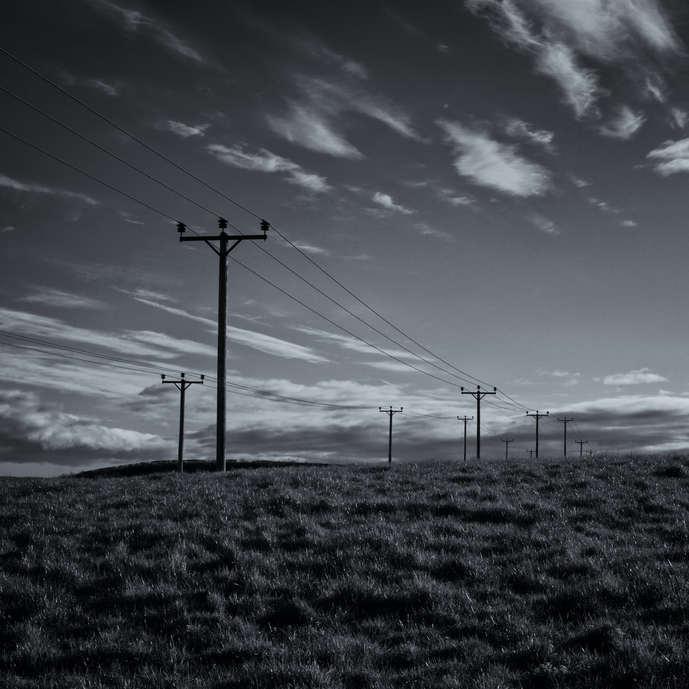 gray electric post under blue sky
