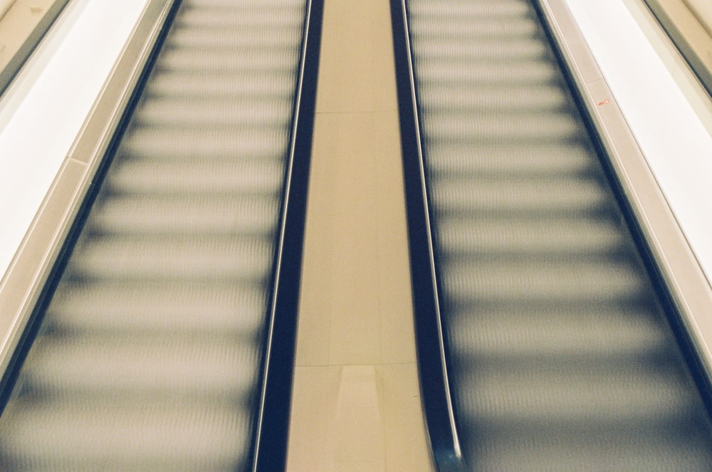 white and blue escalator in a room