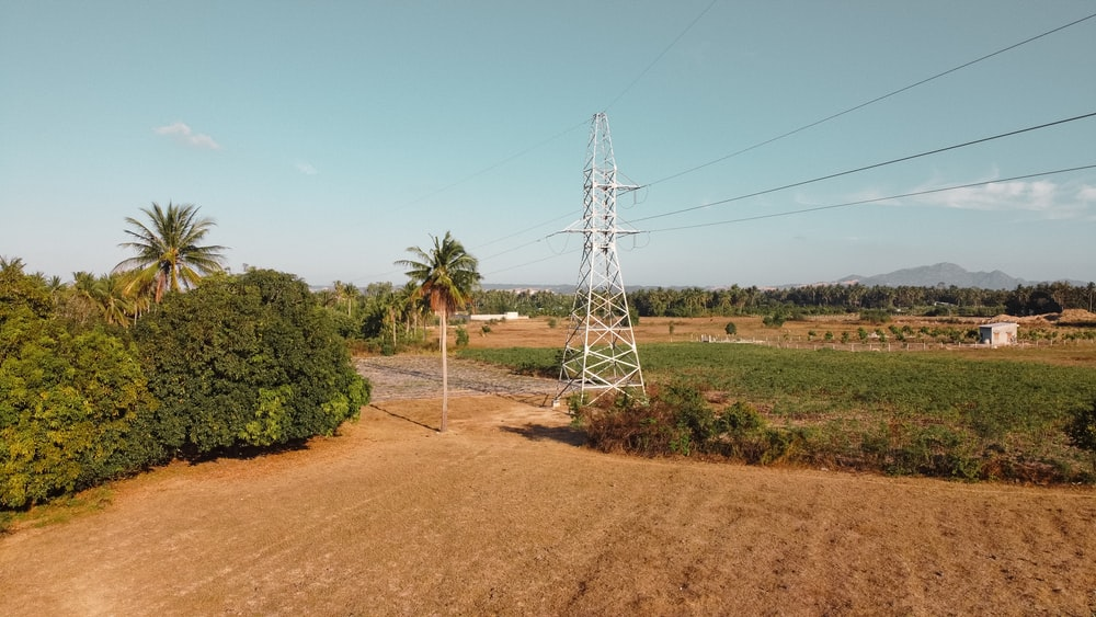 white electric tower on brown field during daytime