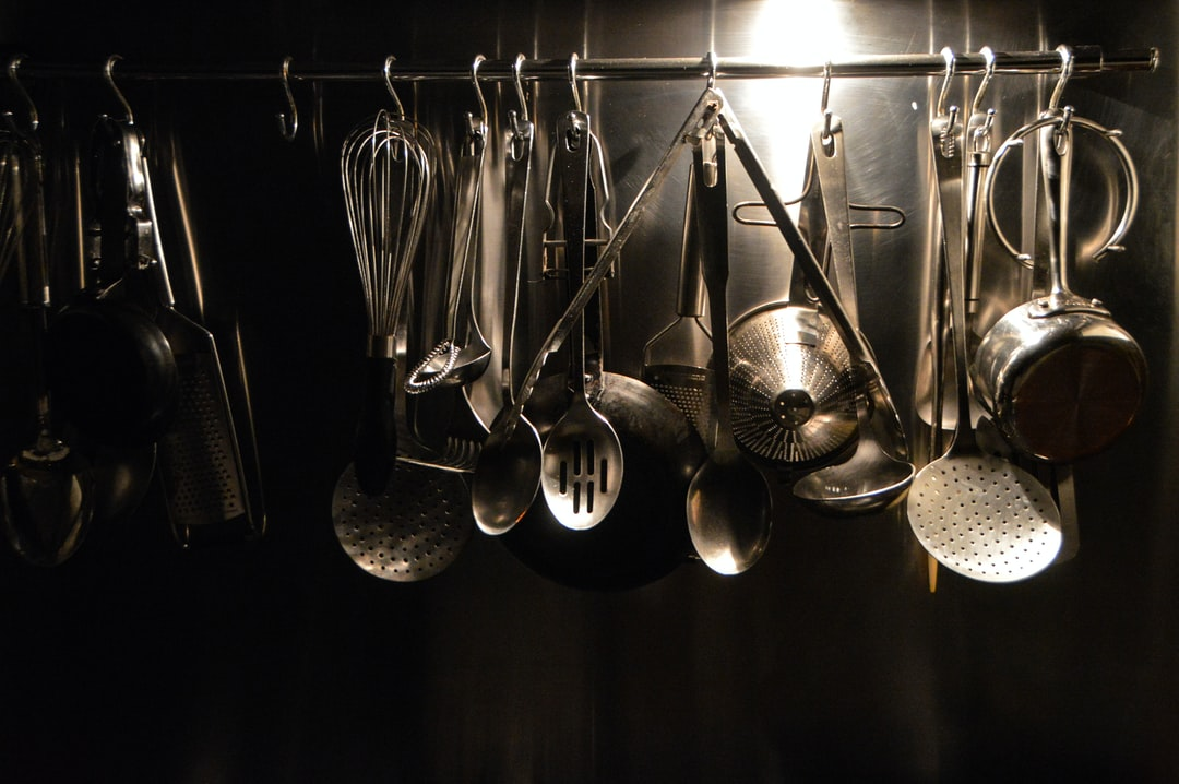 Metal kitchen utensils hinging on a rail. Top lighting and shining edges caught my eye