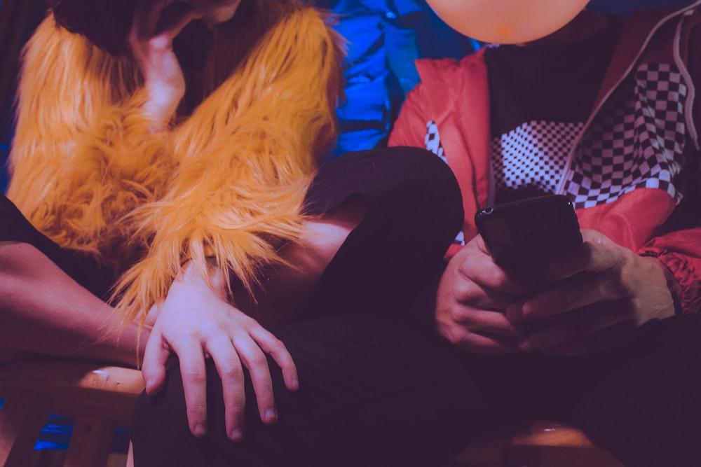 woman in black pants sitting beside woman in blue jacket