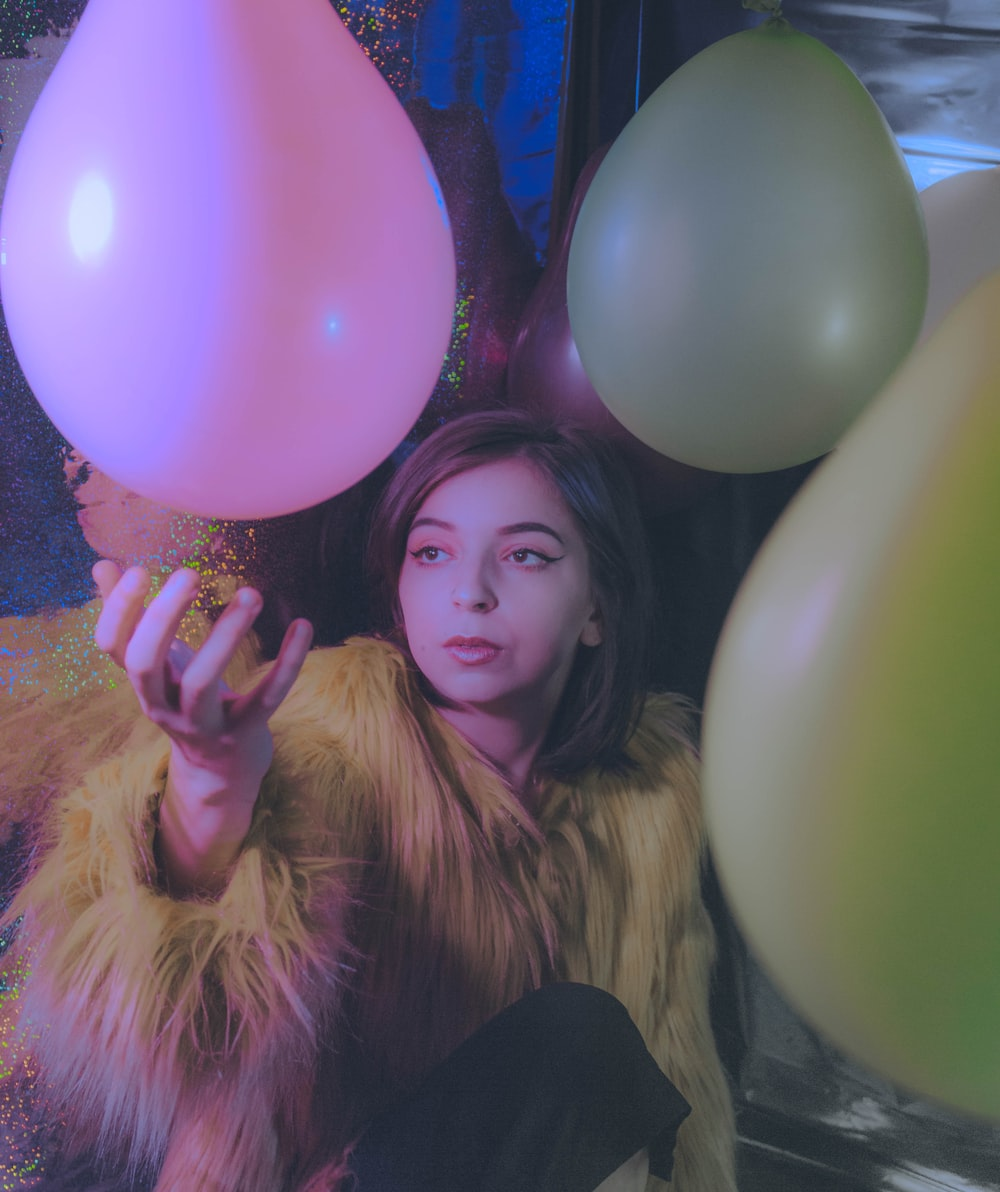 woman in black long sleeve shirt holding pink balloons