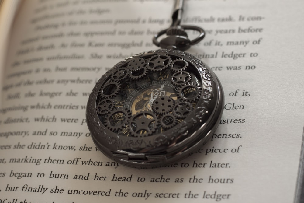 gold round pocket watch on white printer paper