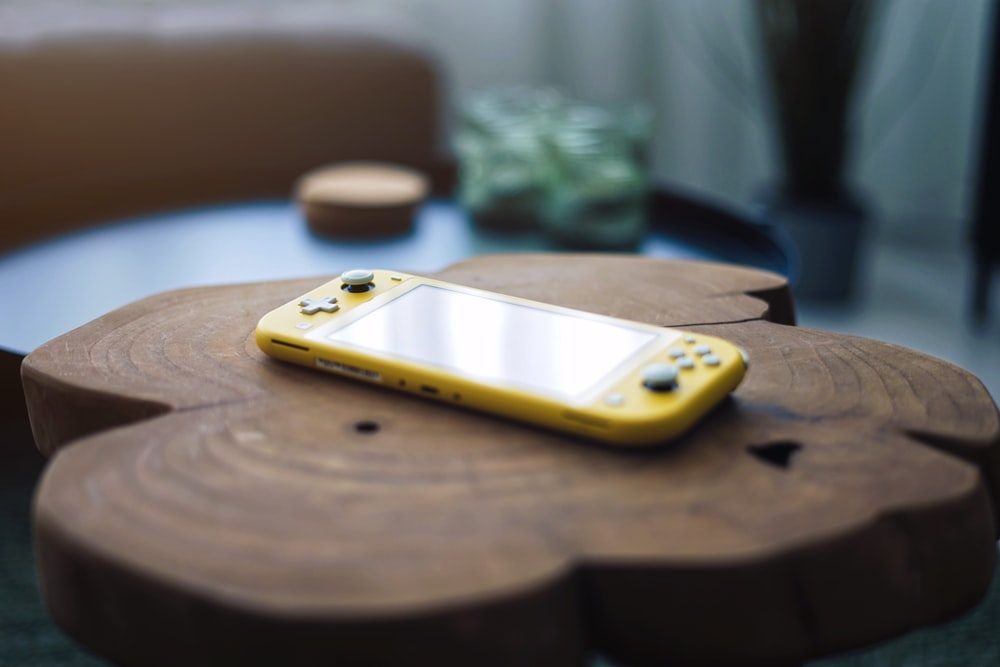 yellow and silver iphone case on brown wooden table