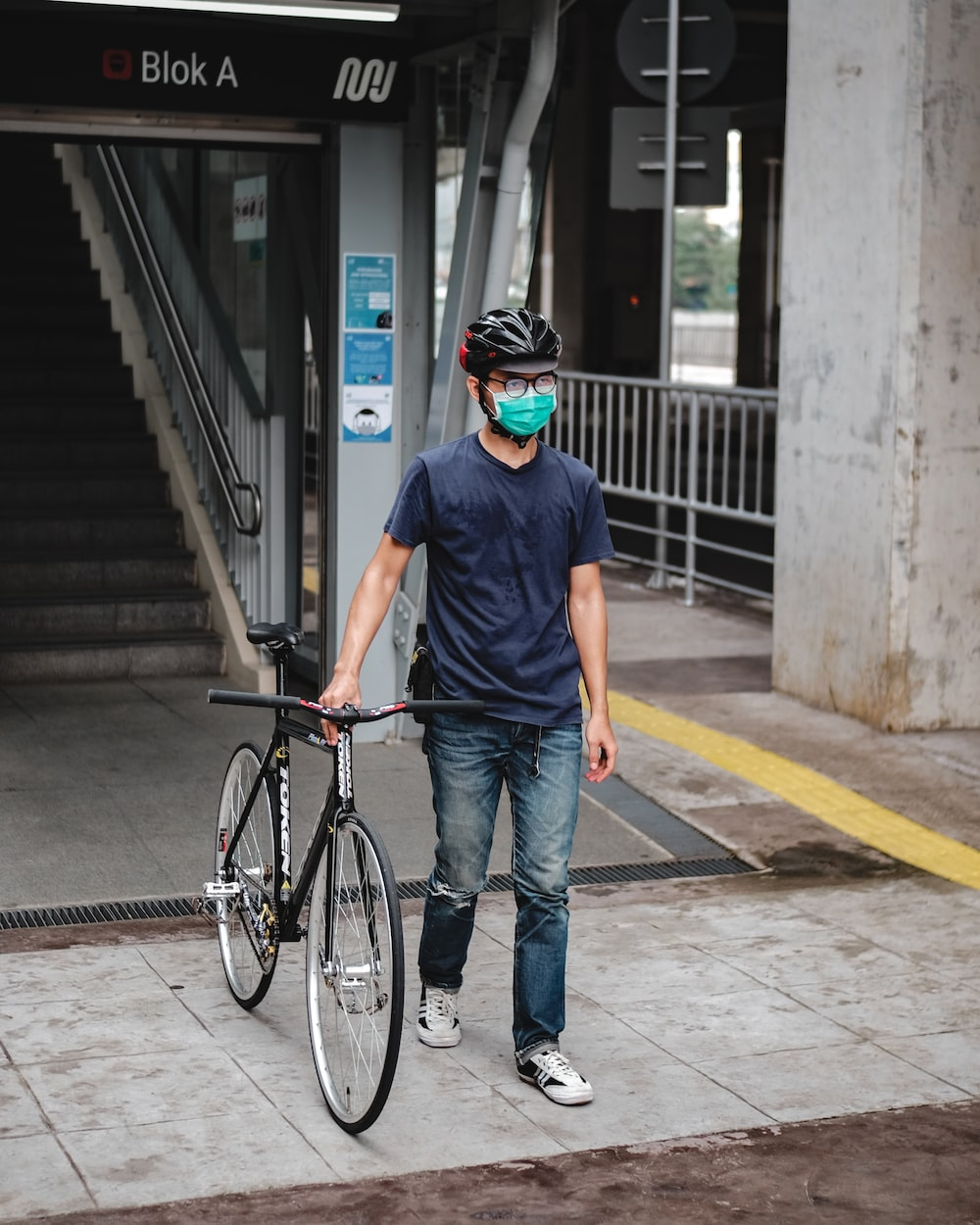 man in blue crew neck t-shirt and blue denim jeans standing beside black bicycle during