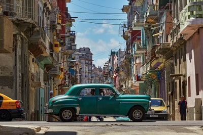 green car parked on side of the road cuba teams background