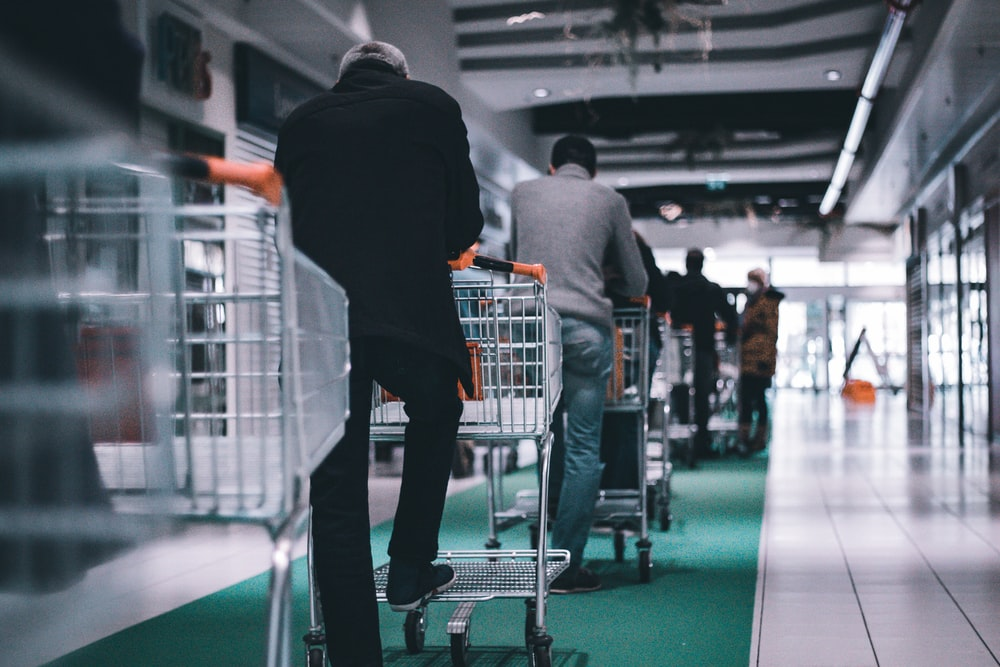 man in black long sleeve shirt and black pants standing on shopping cart