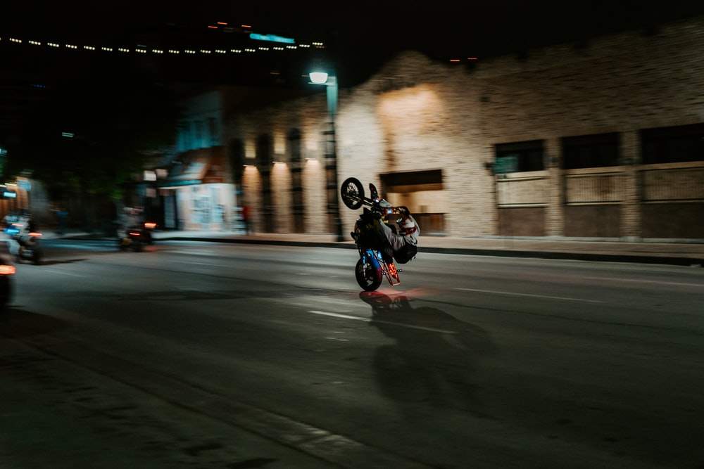 man in black jacket riding motorcycle on road during night time