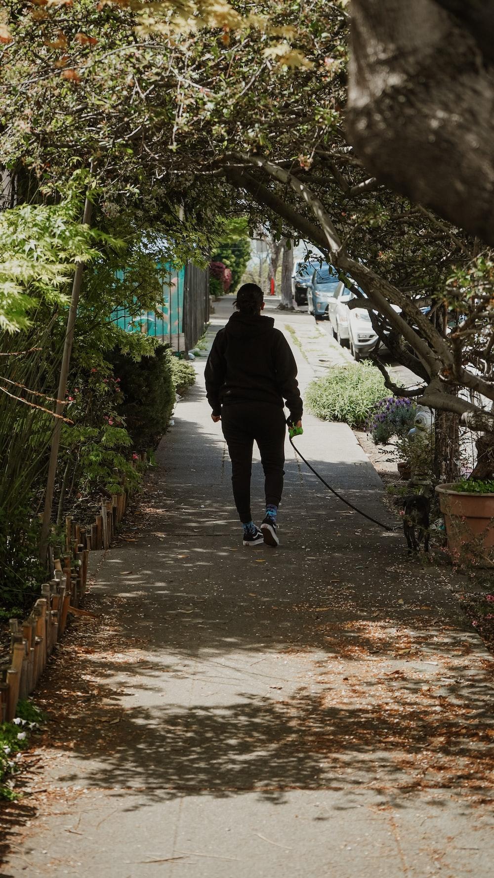 man in black jacket walking on pathway during daytime
