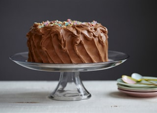 brown cake on clear glass cake stand