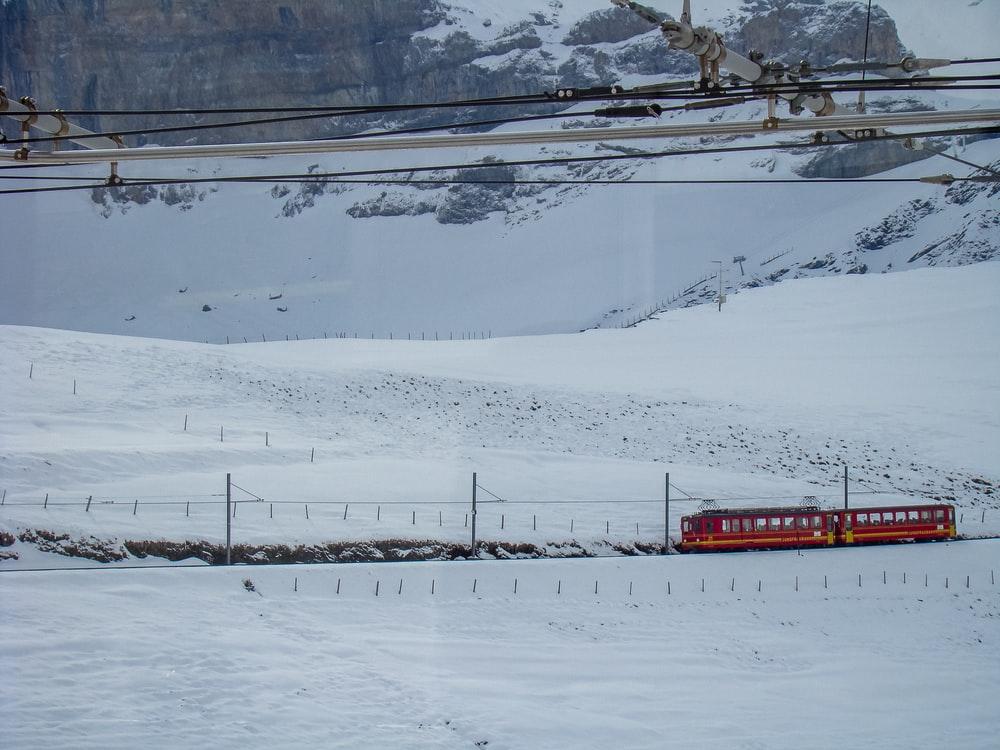 red and white train on snow covered ground during daytime