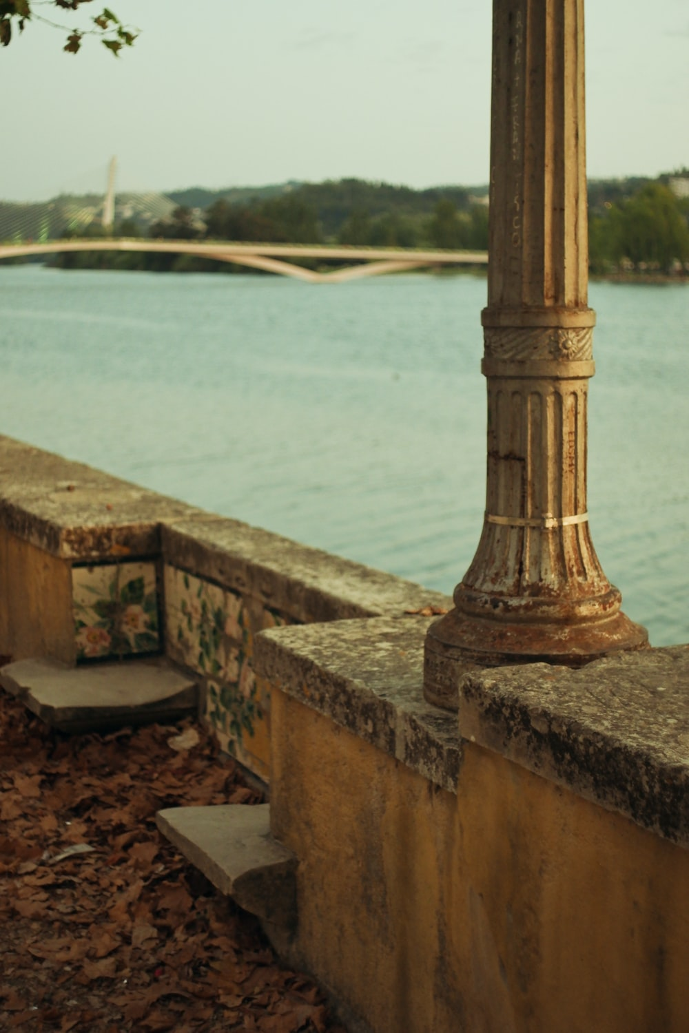 brown concrete post near body of water during daytime