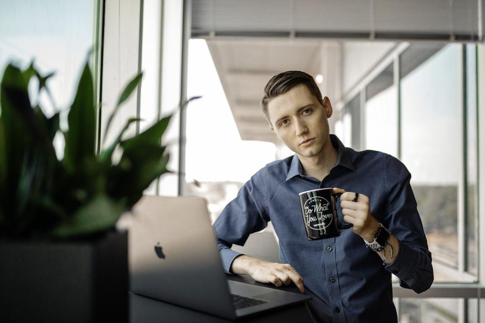 man in blue dress shirt holding black ceramic mug