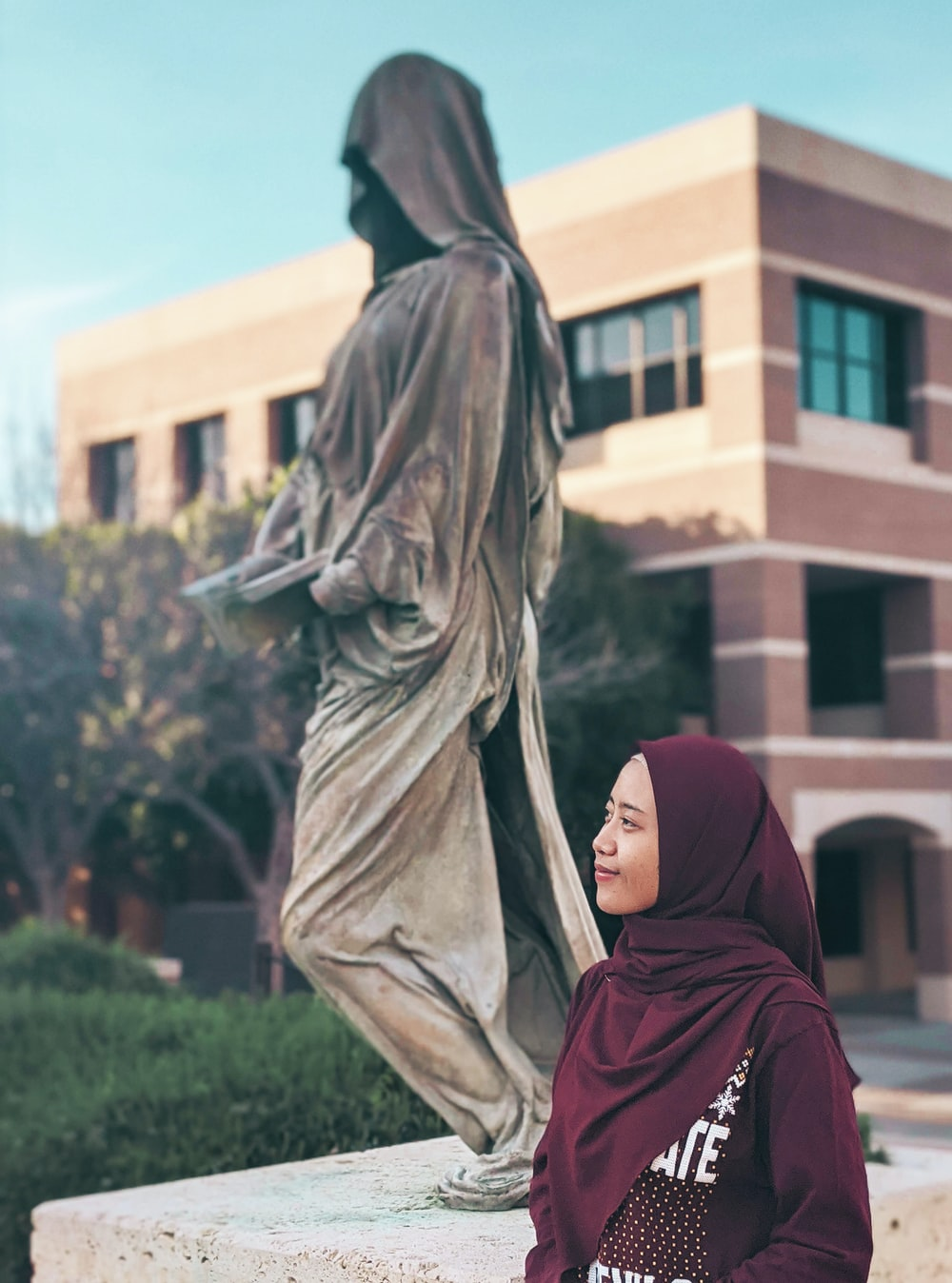 woman in red hijab standing near statue