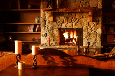 brown wooden table with white pillar candles fireplace teams background