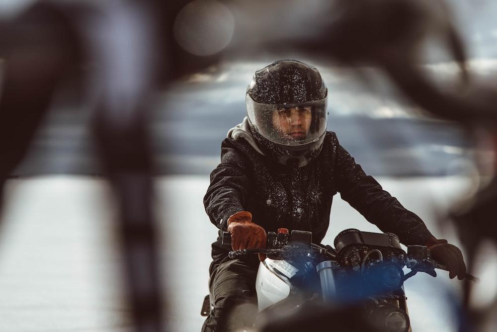 man in black jacket riding blue motorcycle