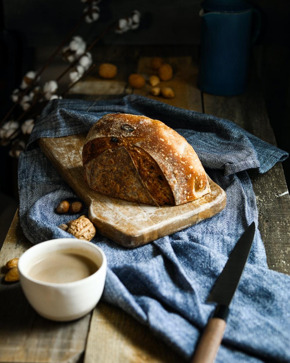 brown bread on brown paper bag beside white ceramic mug