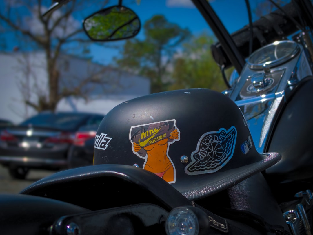 An old school helmet around with Nike stickers rests on the seat of a Harley Davidson Motorcycle.