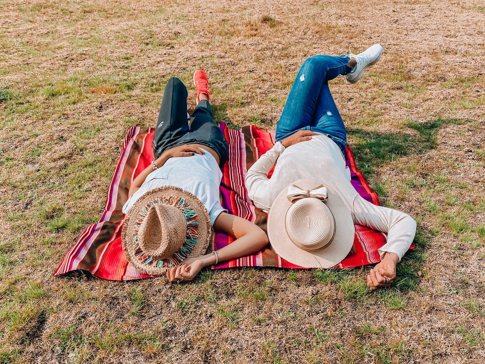 woman in brown sun hat lying on green grass field during daytime