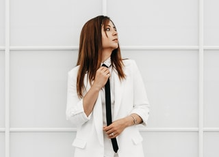 woman in white blazer and white pants standing