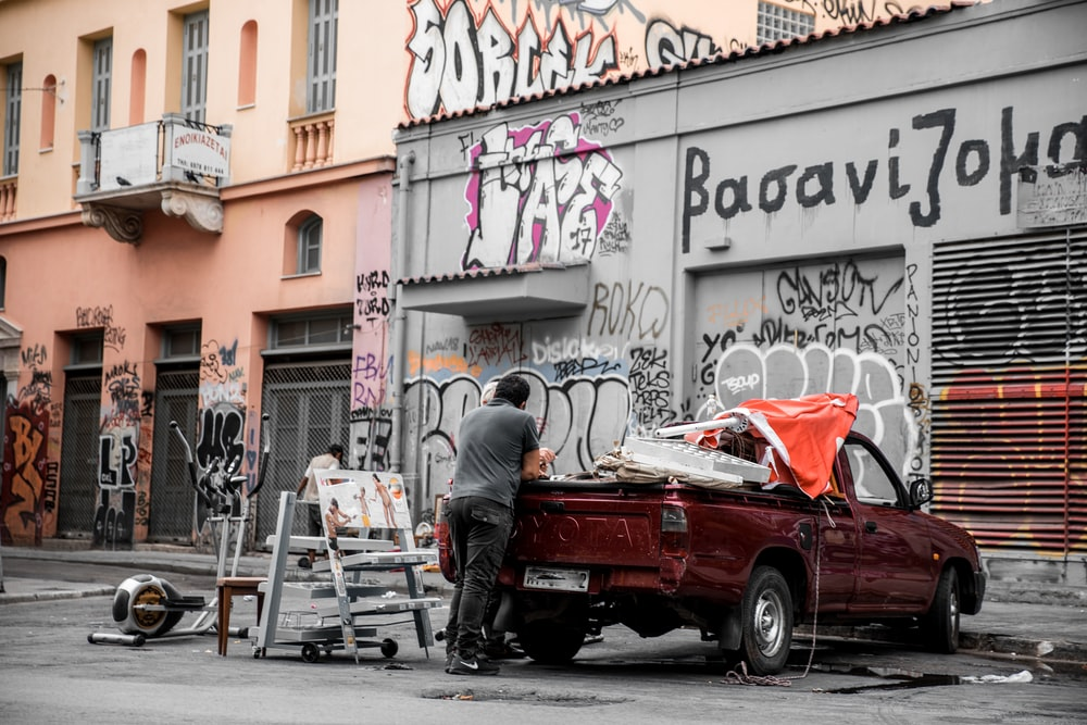 man in black jacket sitting on white wooden chair beside red car during daytime