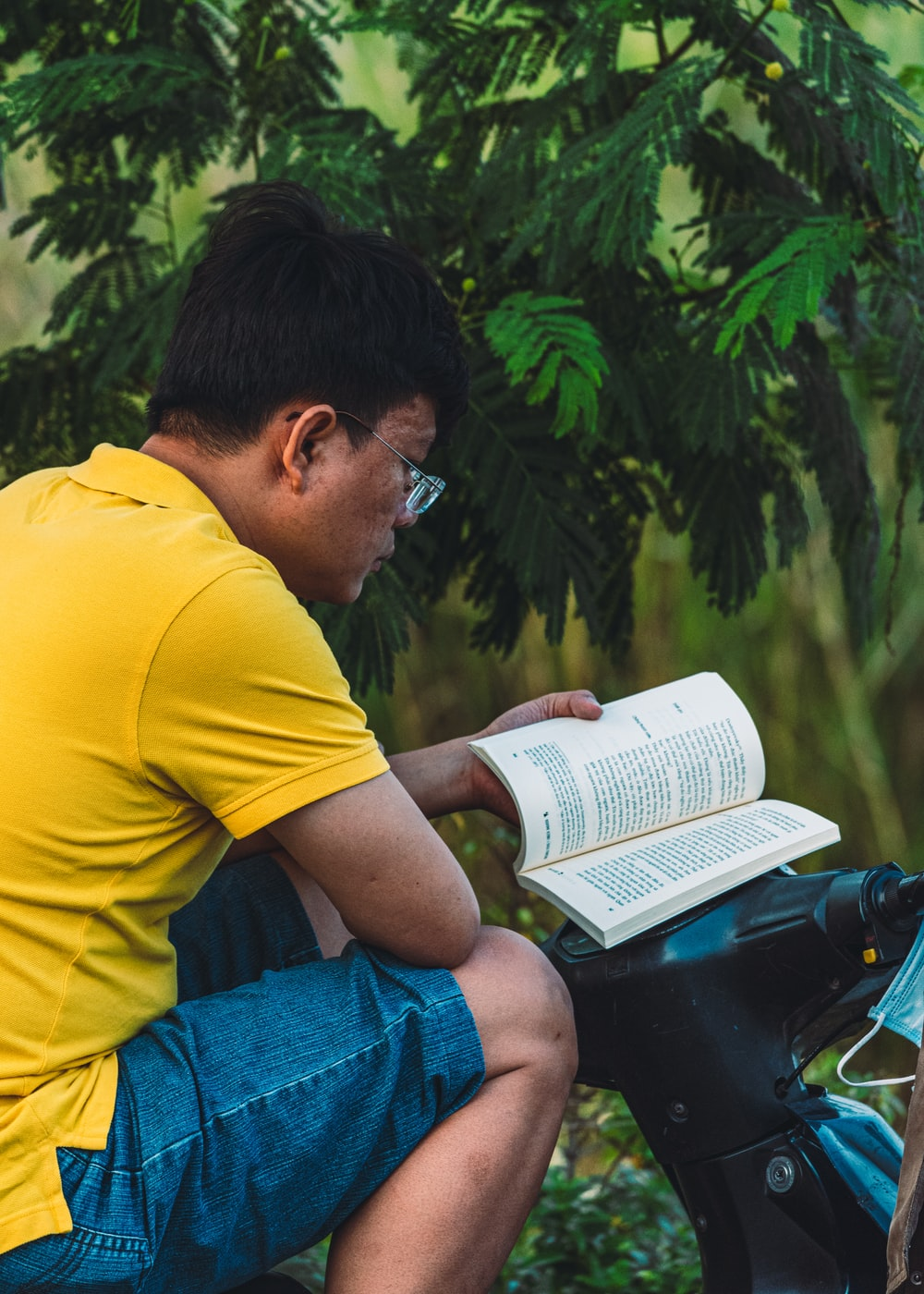 man in yellow t-shirt and blue denim jeans reading book