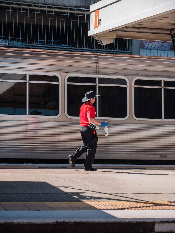 man in red shirt and black pants walking on sidewalk near train station during daytime