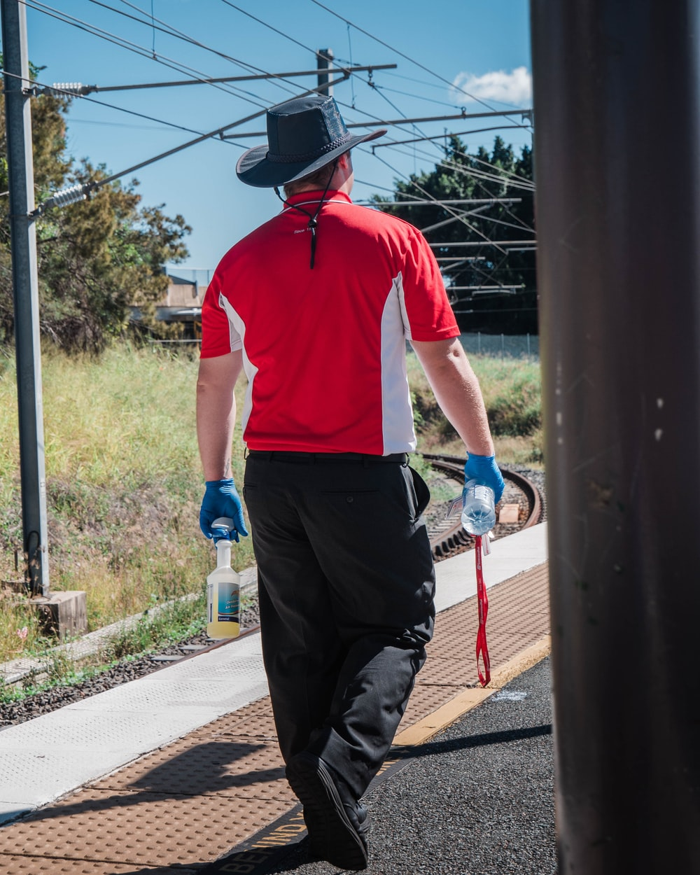 man in red polo shirt and black pants holding blue plastic water bottle