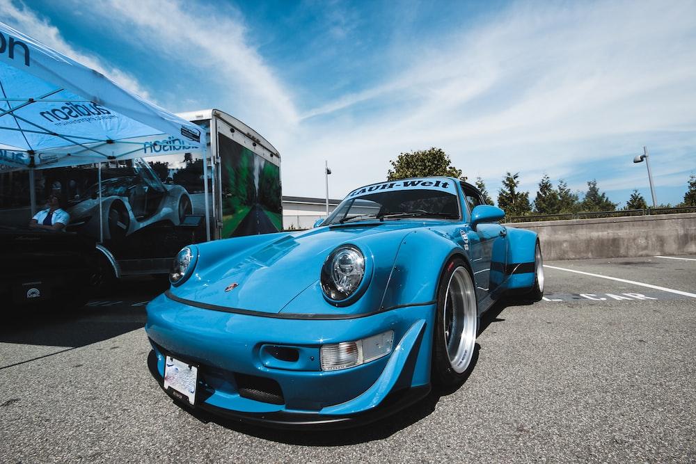 blue chevrolet camaro parked on gray asphalt road during daytime