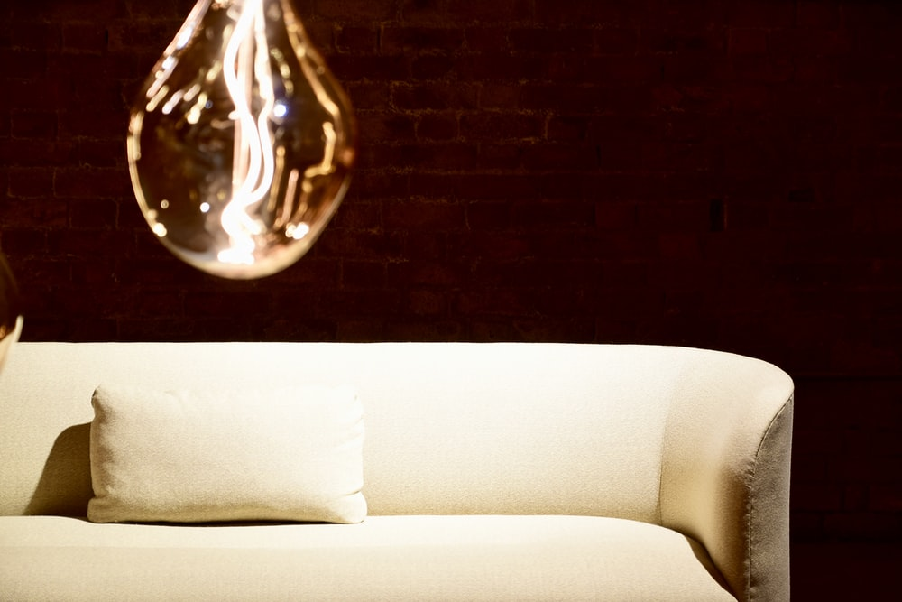 clear glass light bulb on white couch