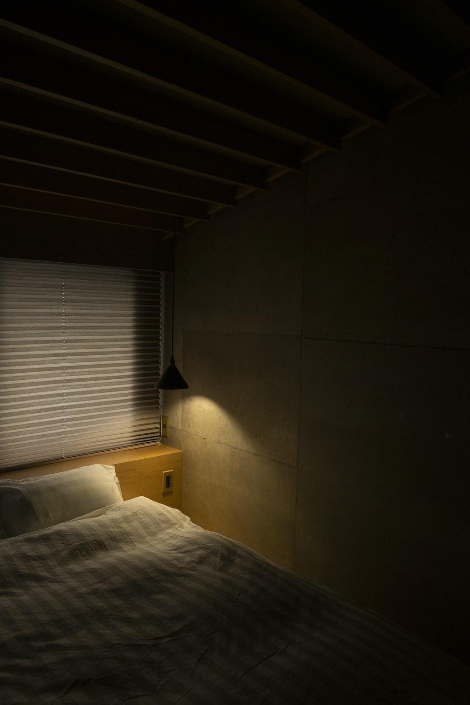 white bed linen near white window blinds