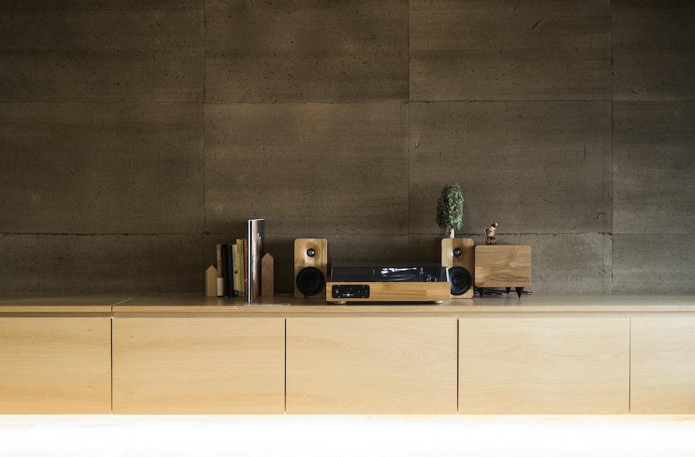 brown and black speaker on brown wooden shelf
