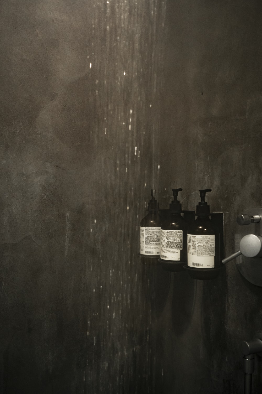 grayscale photo of bottles on wooden table