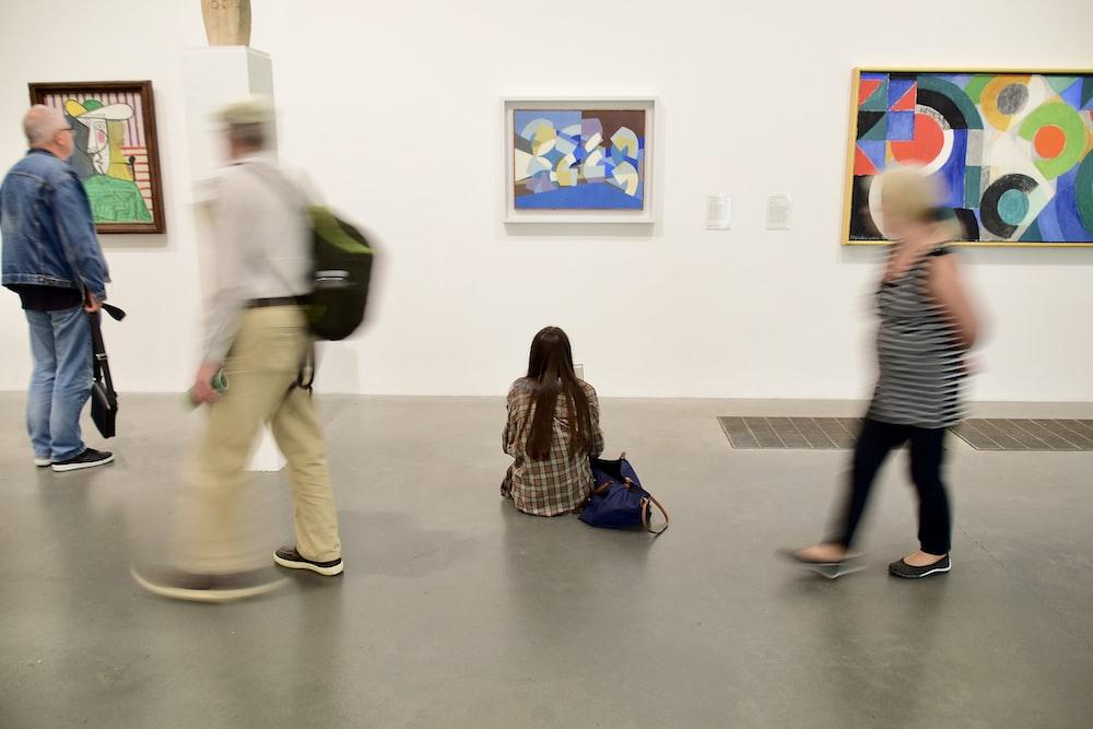 people walking on hallway with paintings