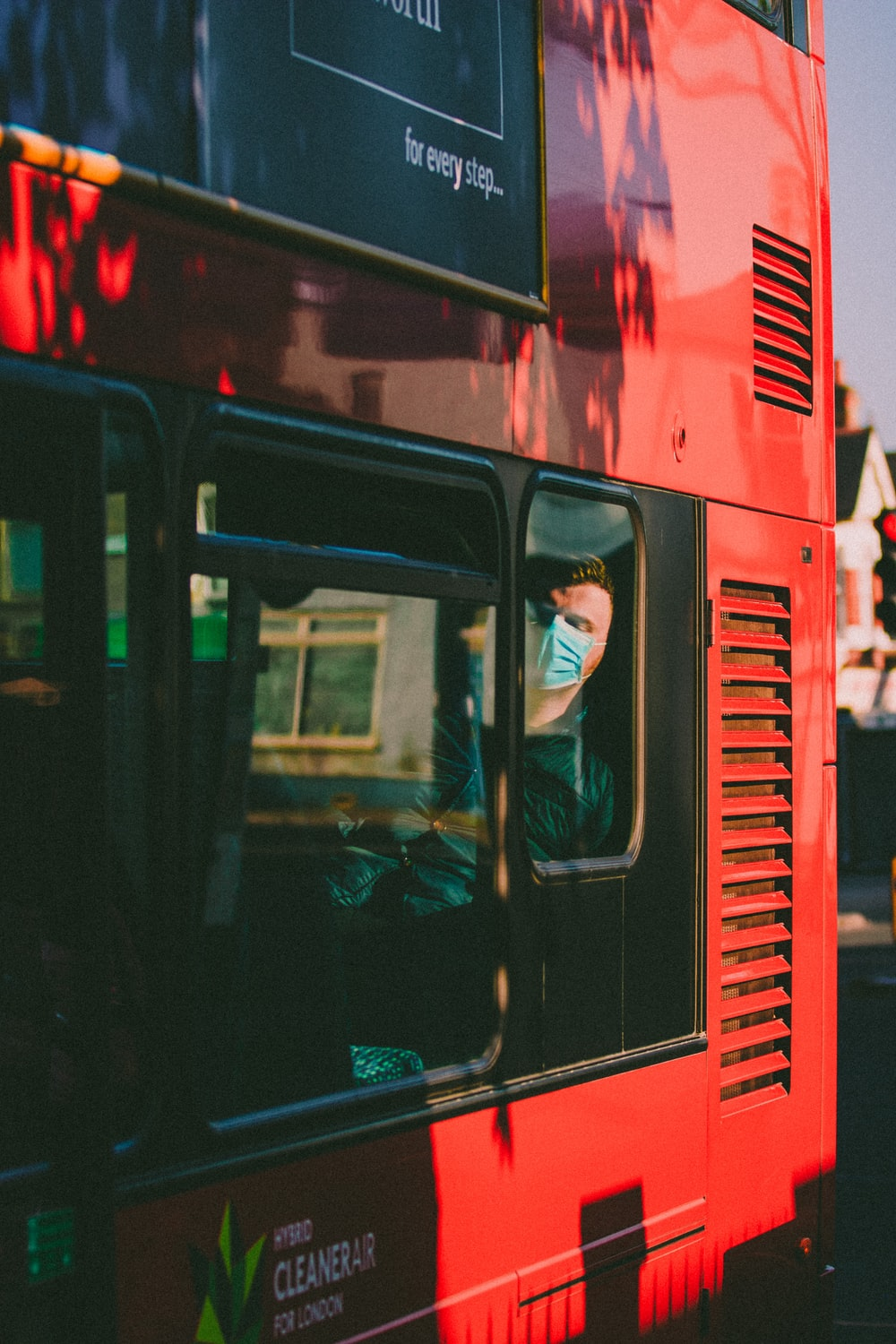 man in black jacket inside red bus
