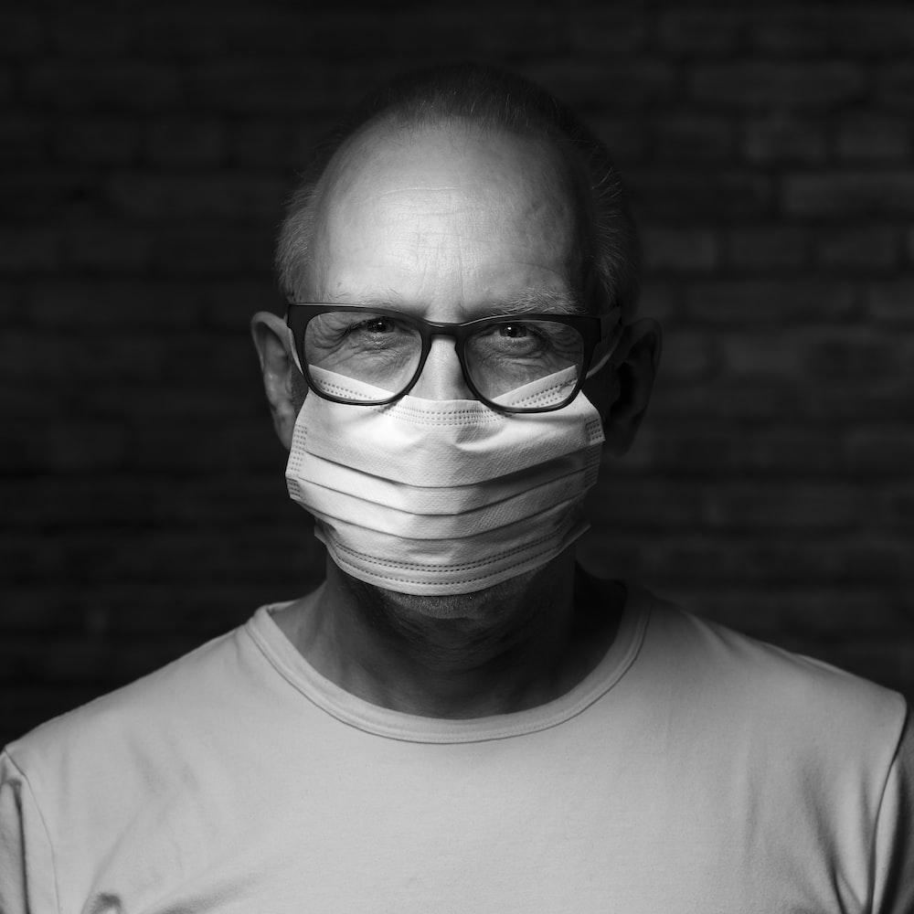man in crew neck shirt wearing eyeglasses