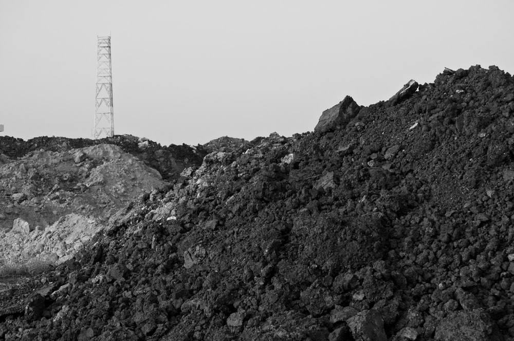 grayscale photo of mountain with tower