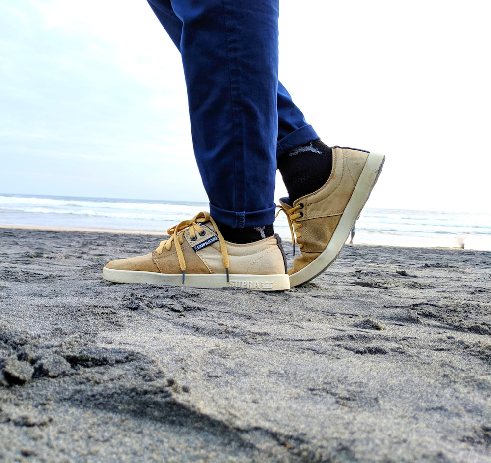 person in blue denim jeans and brown and white sneakers standing on beach during daytime