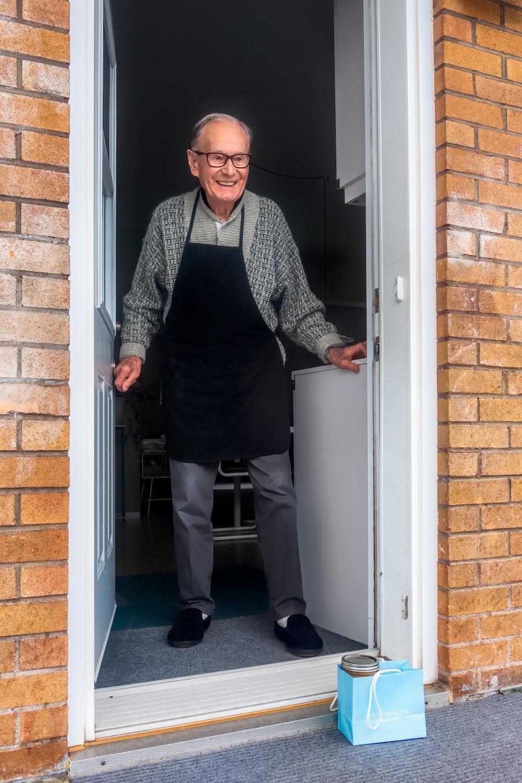 man in black vest and black dress pants standing beside white wooden door
